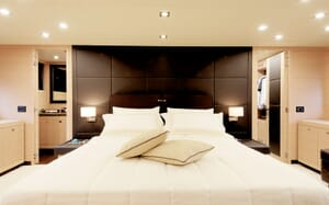 Motor yacht KAWAI master suite with white bed linen, dark wood interiors with soft lighting