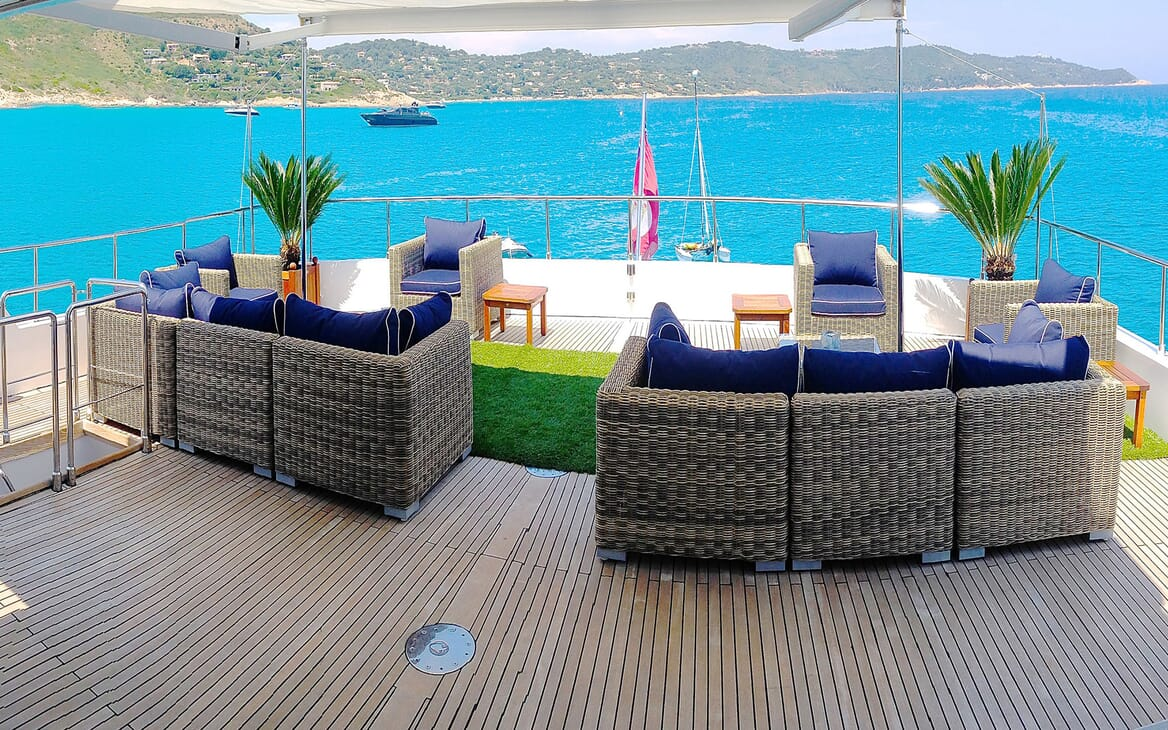 Motor yacht MIRAGGIO aerial shot of top deck with wicker seating and parasoli
