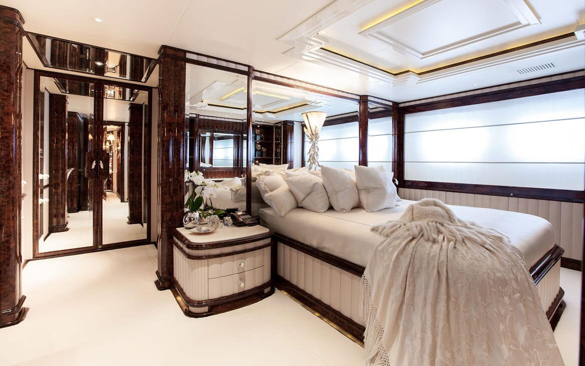 Motor yacht LIONESS V master suite with white bed linen and dark wood finishes