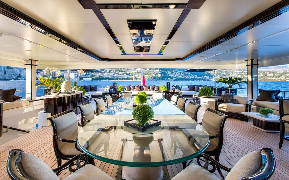 Motor yacht LIONESS V deck shot with large glass dining table and surrounding seating