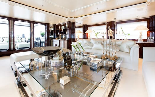Motor yacht LIONESS V living room with large windows, glass coffee table and white seating