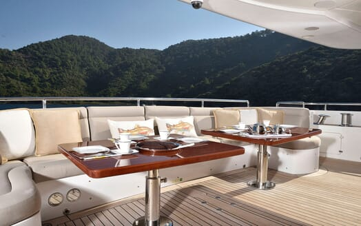 Motor yacht Quest alfresco dining area with views of mountainous landscape in background