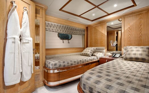 Motor yacht Quest twin stateroom with stone colour bed linen and wood surroundings