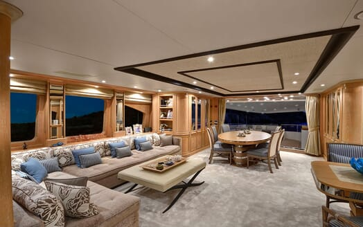 Motor yacht Quest living and dining room at night with soft furnishings
