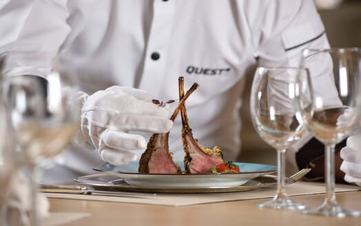 Motor yacht Quest chef serving lamb shank with glassware on table