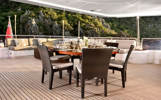 Motor yacht Quest deck with alfresco dining table with glassware and views of mountainous landscape
