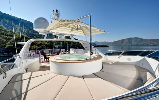 Motor yacht Quest jacuzzi on deck with umbrella and views of mountainous landscape