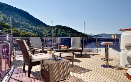 Motor yacht Quest upper deck with seating area and bar with views of mountainous landscape and water