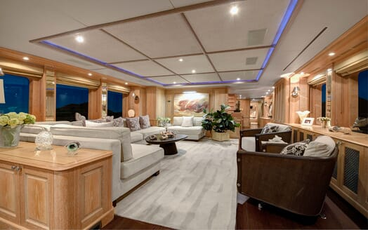 Motor yacht Quest living room with stone colour sofa and rug, wood surroundings and low ceiling lighting