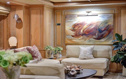Motor yacht Quest living room with stone colour sofa and rug, wood surroundings and painting mounted onto wall