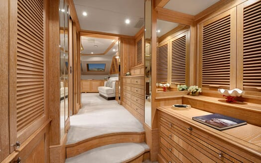 Motor yacht Quest master suite corridor with wood cabinets, mirrors and cream carpet