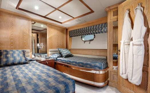 Motor yacht Quest twin stateroom with blue bed linen and wood surroundings