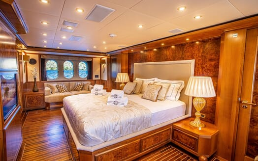 Motor yacht Milaya master suite with gold and white bed linen and soft sofa under window