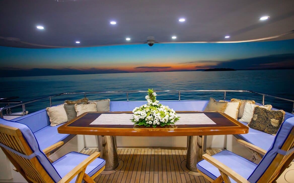 Motor yacht Milaya deck with alfresco seating area with sunset in background
