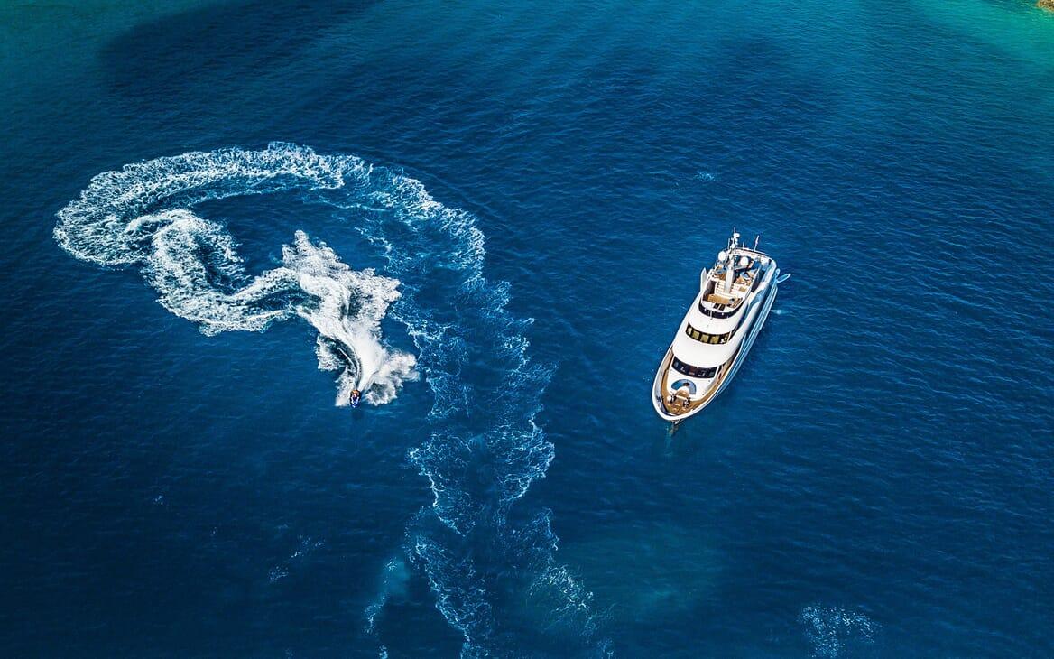 Motor yacht Milaya high aerial shot with jetski on water