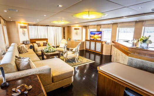 Motor yacht Milaya living room with dark wood flooring and gold and silver furnishings