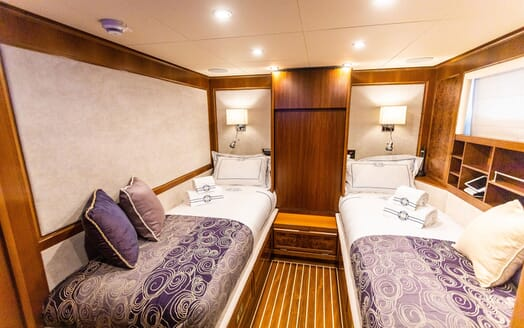 Motor yacht Milaya twin stateroom with white and purple bed linen