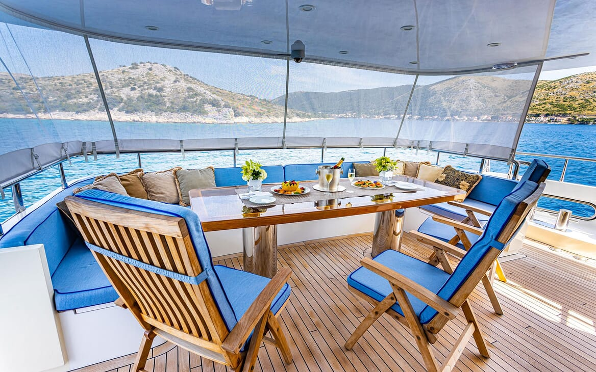 Motor yacht Milaya deck with alfresco dining table and blue seating