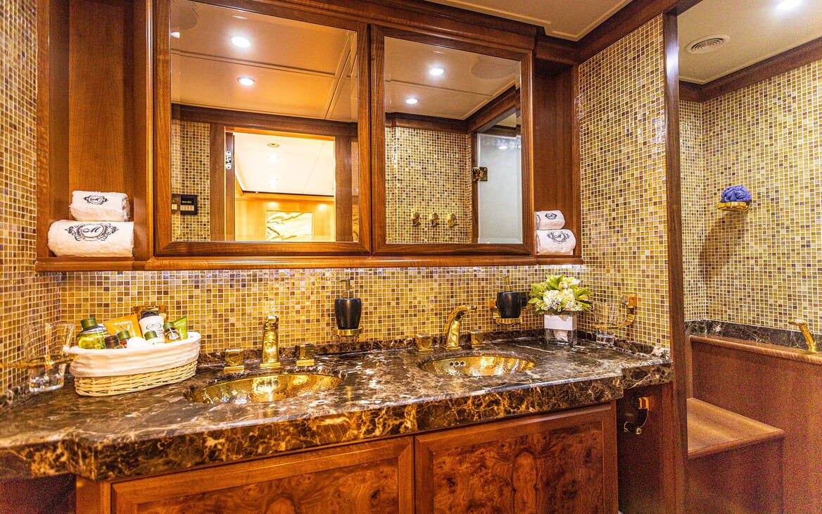 Motor yacht Milaya bathroom with brown and gold mosaic tiles and gold plated taps