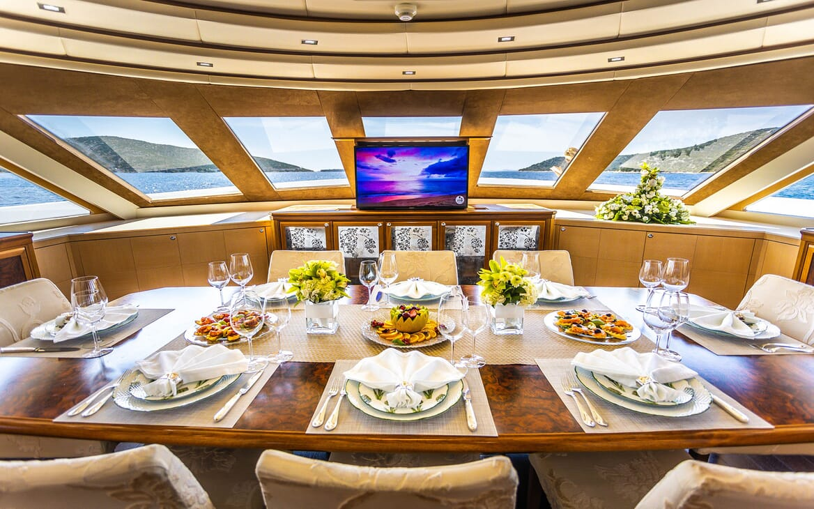 Motor yacht Milaya dining room with large table with plasma TV and seaviews