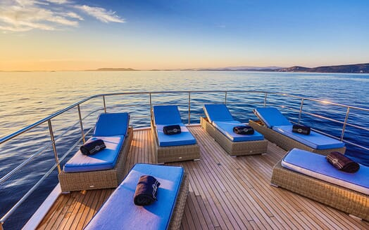 Motor yacht Milaya deck with blue sunloungers and seaviews