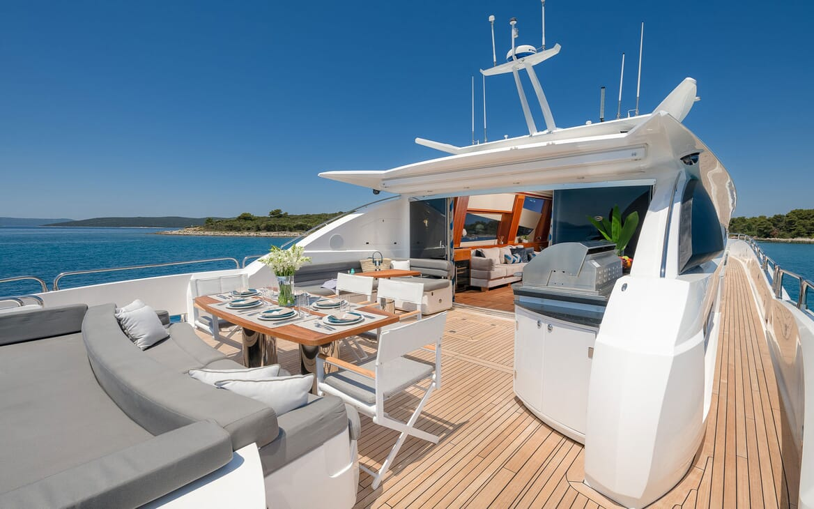 Motor Yacht Quantum aerial deck shot of alfresco dining table and seating area, views of blue sky and sea