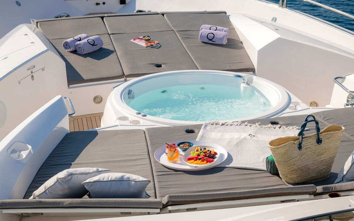 Motor yacht Quantum aerial shot of jacuzzi and sun loungers, fruit salad and beach towels