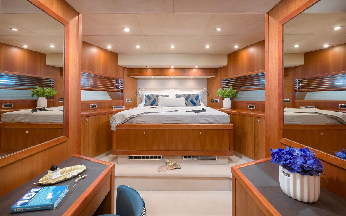 Motor yacht Quantum stateroom with oak surroundings and purple flowers