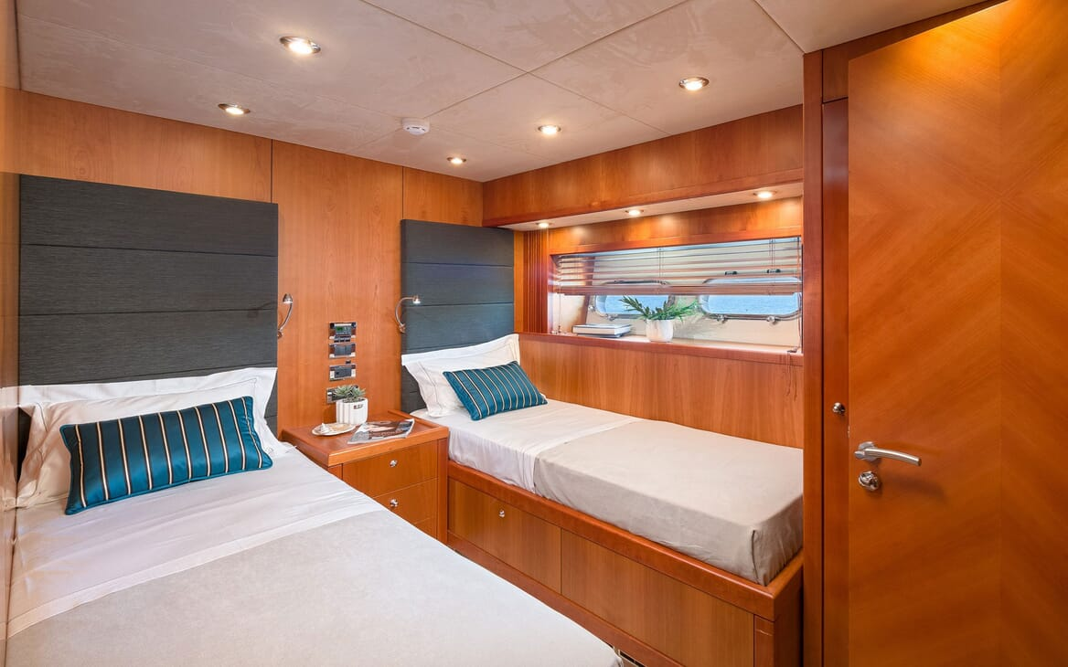 Motor yacht Quantum twin cabin with white bed linen and oak surroundings, window with blinds with view of water