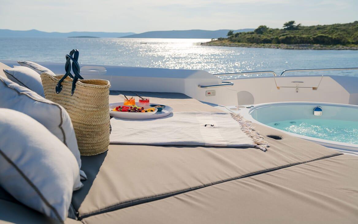 Motor yacht Quantum sun lounge shot with fruit salad, beach bag and jacuzzi