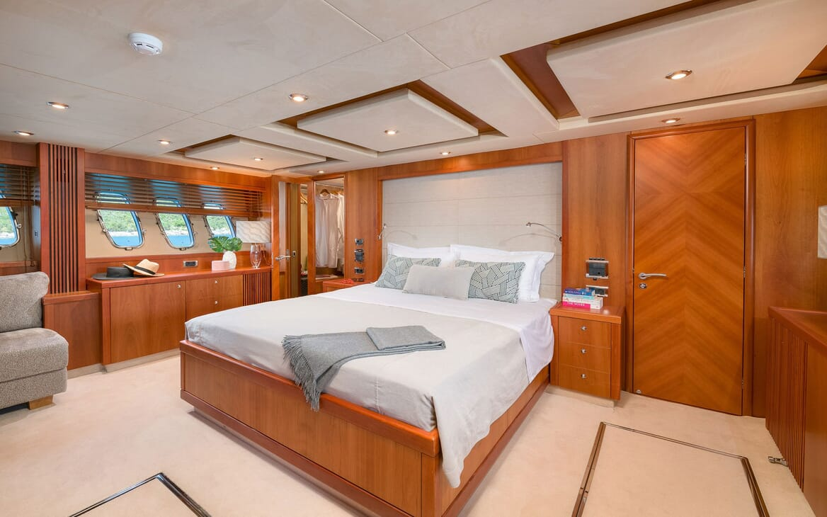 Motor Yacht Quantum master suite with white bed linen and oak furniture and surroundings