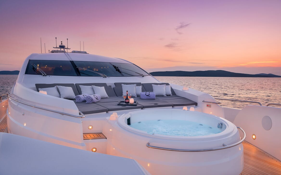 Motor yacht Quantum front deck shot with jacuzzi and refreshments with views of sunset