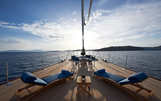 Sailing Yacht Melek deck shot with blue sun loungers and alfresco dining table