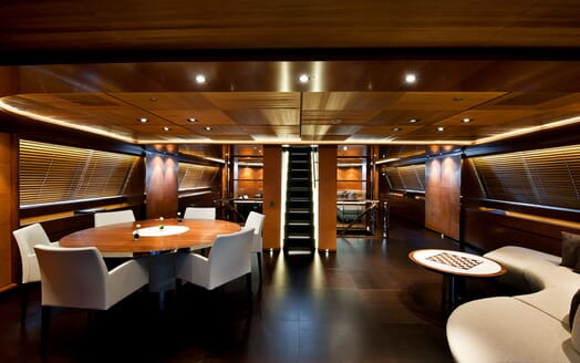 Sailing Yacht Melek dark wood living room and dining room furnishings with low ceiling lighting