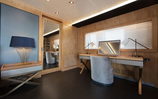Motor yacht BEATRIX master suite with contemporary interiors, cosmetic desk and door mirror