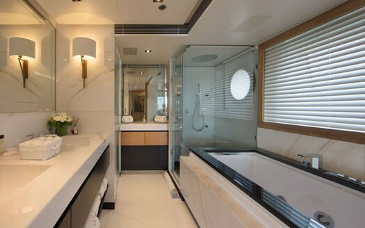 Motor yacht BEATRIX master suite bathroom with large bath tub, twin sinks, large shower and mirror