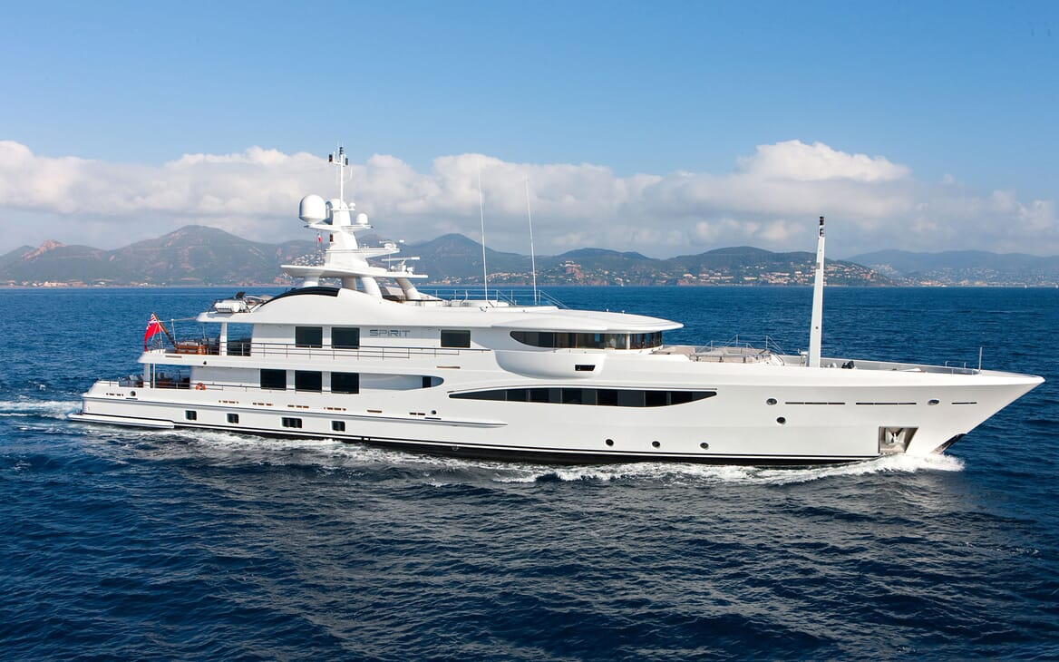 Motor yacht Spirit right side hero shot on water, views of coast and blue sky