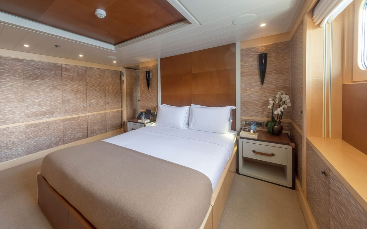 Motor yacht Spirit interior shot of master suite, natural wood colour interiors with white bed spread