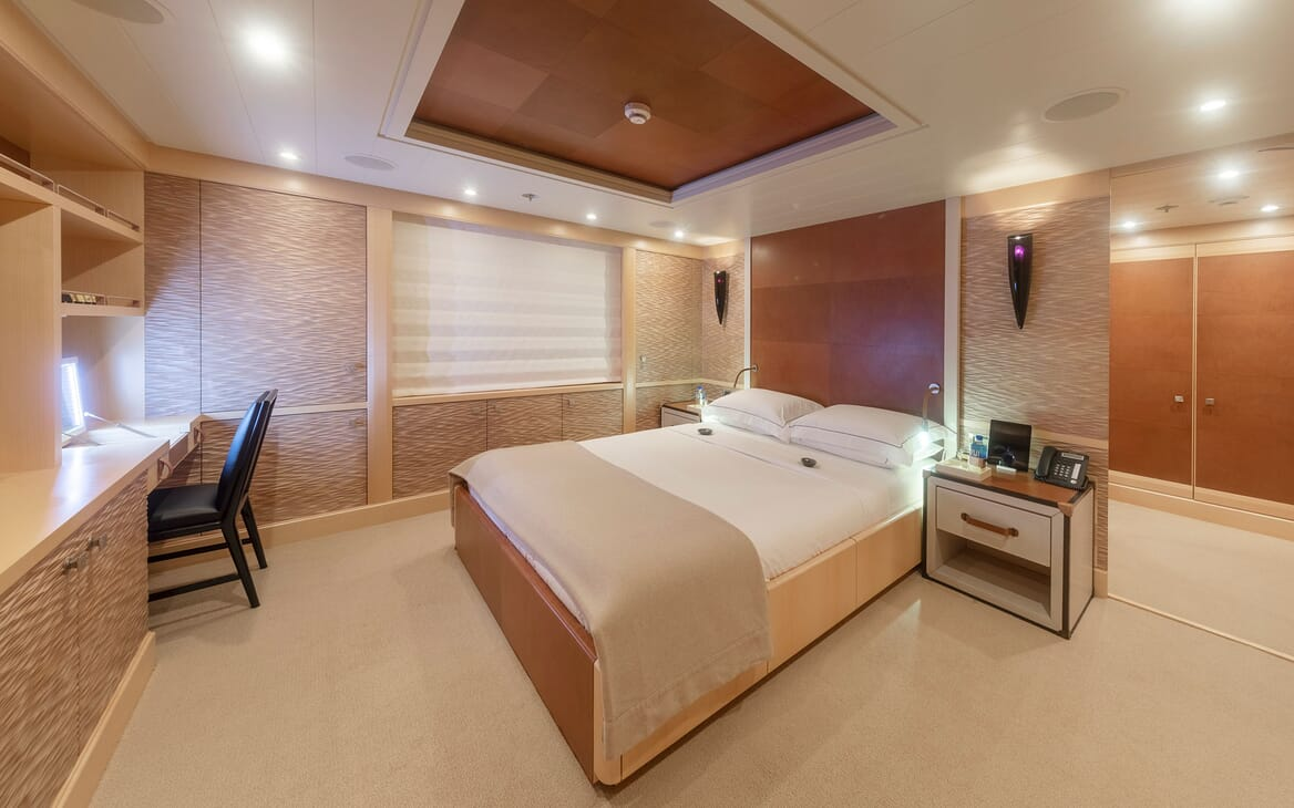 Motor yacht Spirit stateroom with white bed linen, oatmeal carpet and desk