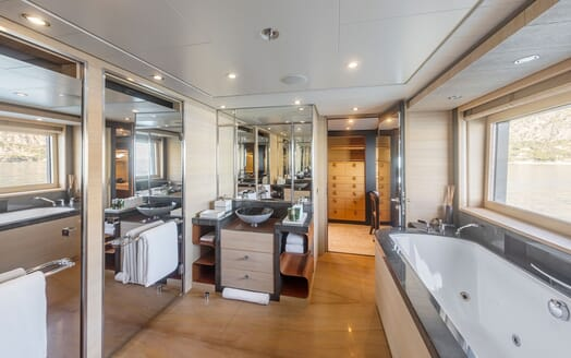 Motor yacht Spirit stateroom ensuie with jacuzzi bath tub, sink with large mirror and walk in wardrobe