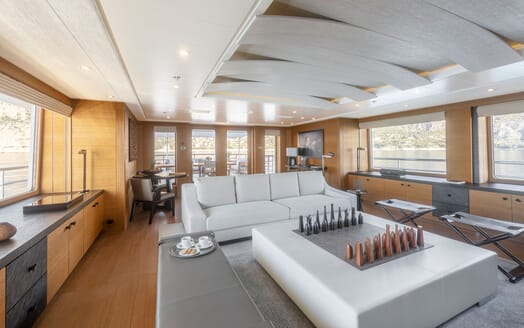 Motor yacht Spirit interior living room shot with grey furnishings, wood surrounding and large chess board in centre of room