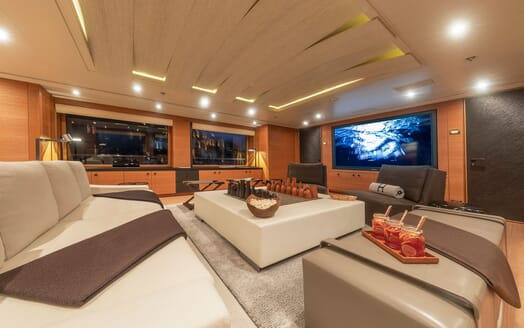 Motor yacht Spirit interior living room shot at night with grey furnishings, wood surrounding and large plasma TV on wall