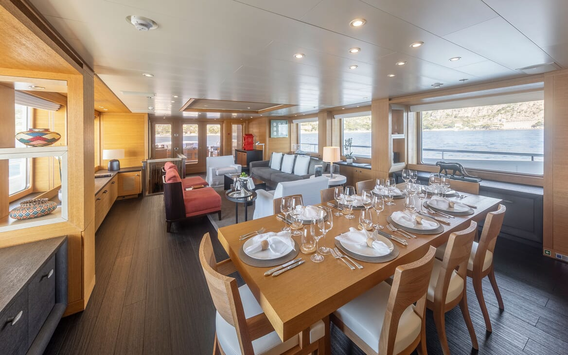 Motor yacht Spirit interior dining room and living room, with wood flooring and laid table, views of water and coast