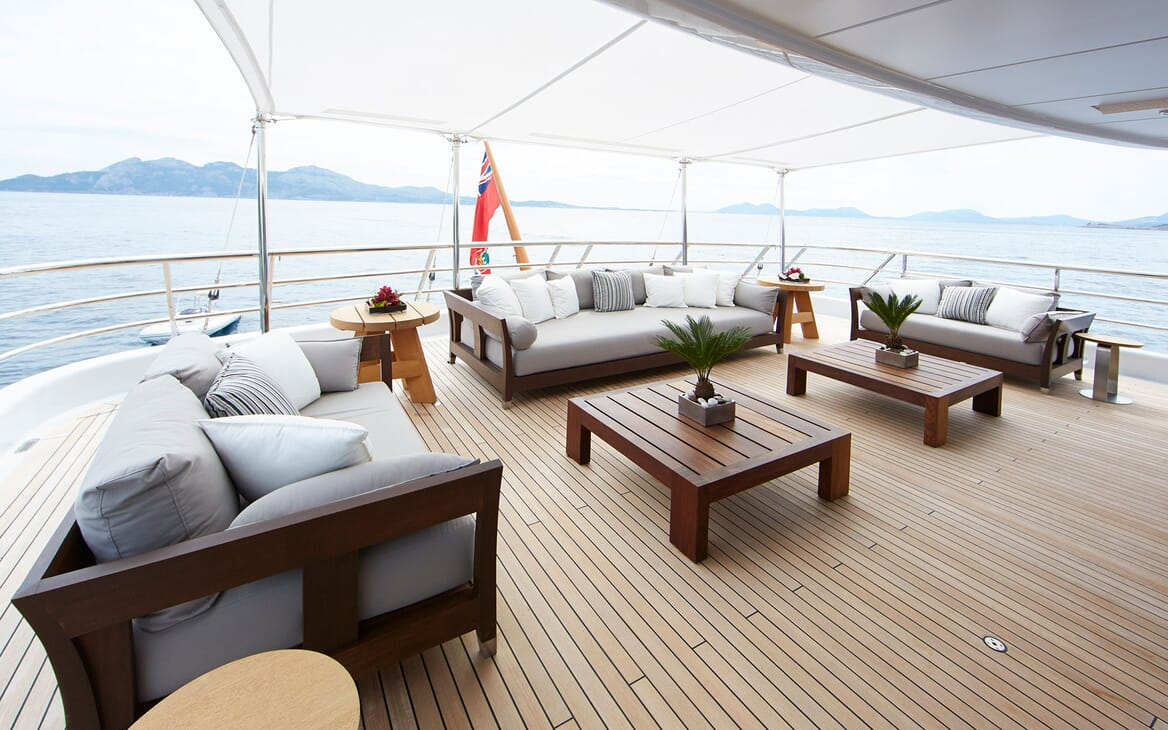 Motor yacht Spirit deck shot, grey three piece outdoor furniture, coffee tables and sea views