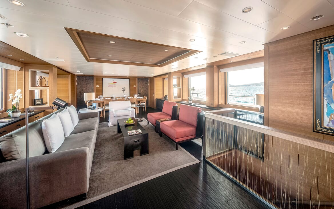 Motor yacht Spirit living room with grey velvet sofa and opposing red velet armchairs and sea views
