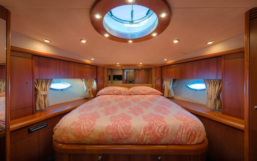 Motor Yacht GLORIOUS bedroom 2 with pale pink bedspread and round skylight