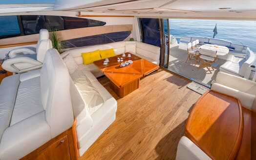 Motor Yacht GLORIOUS aerial dining area shot wood flooring door open to deck