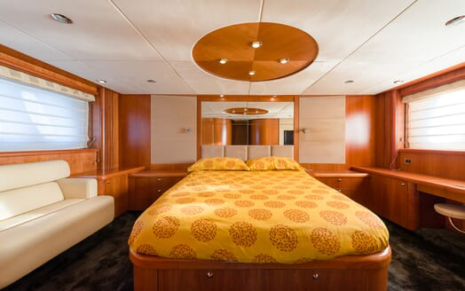 Motor Yacht GLORIOUS master suite with yellow bedspread and large windows