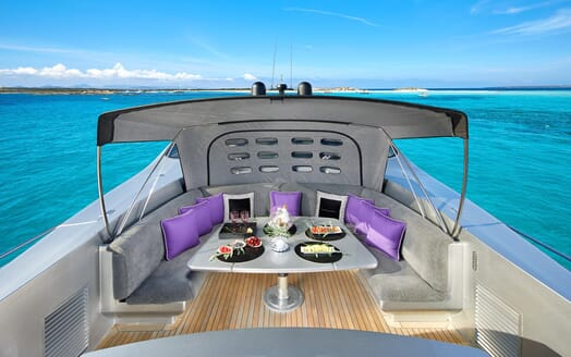 Motor Yacht SHALIMAR II top deck area with grey and purple furnishings, views of turquoise water and alfresco dining area