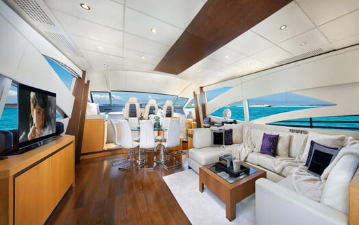 Motor Yacht SHALIMAR II living room with dark wood floors, cream sofa with soft furnishings and views of turquoise water